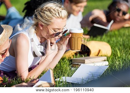 beautiful multiethnic girls reading books while lying on grass and studying in park
