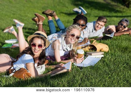 Cheerful Young Multiethnic Students Reading Books While Lying On Green Grass In Park