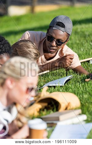 young african american man in sunglasses looking at classmates studying with books on grass