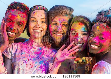 Happy Young Multiethnic Friends Having Fun With Colorful Powder At Holi Festival Of Colors
