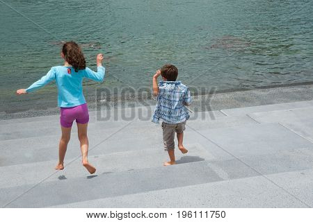 Auckland, New Zealand - January 3, 2012; Obviously enjoying the feeling of freedom children running down steps to waters edge