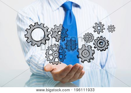 Close up of businessman sitting at table and showing gear mechanism in palms