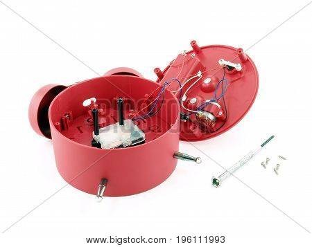 mechanical device of broken red alarm clock with small metal screwdriver and screws isolated on white background, clock repair