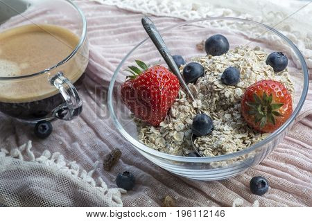 One usual glass bowl with old teaspoon, cereals, strawberries and blueberries, coffee on the pink tissue