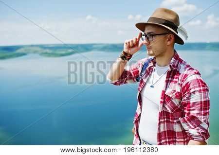 Portrait Of A Hipster In A Hat Admiring Breathtaking View Of Lake Surrounded By Hills.