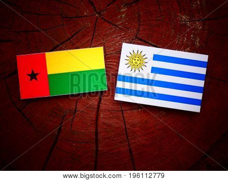 Guinea Bissau Flag With Uruguaian Flag On A Tree Stump Isolated