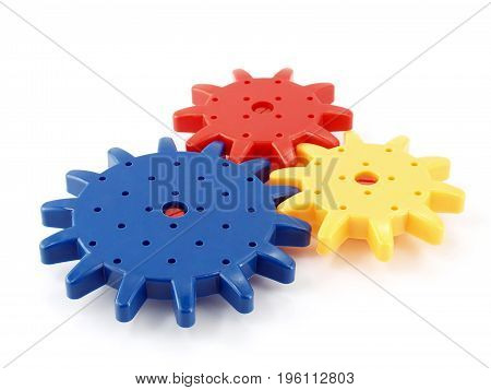 closeup colorful plastic gear isolated on white background, toy that looks like an engine parts for kid learning