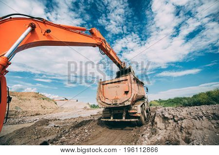 Industrial Working Excavator Loading Dumper Truck During Earthworks, Highway Construction Site And S