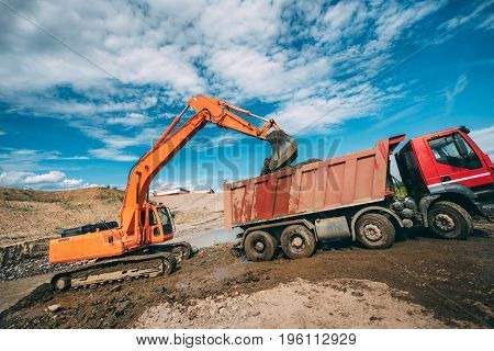 Heavy duty machinery working on construction site - excavator loading dumper trucks during roadworks at highway