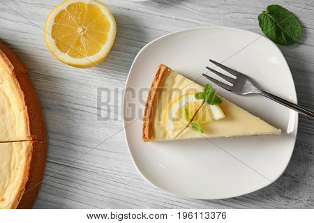 Plate with delicious cheesecake and fork on wooden table