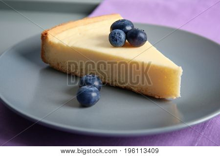 Plate with slice of delicious cheesecake and blueberry, closeup