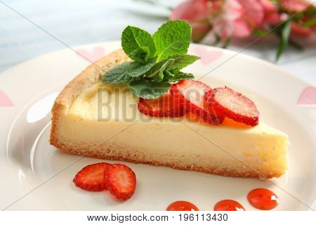 Plate with delicious cheesecake and sliced strawberry, closeup