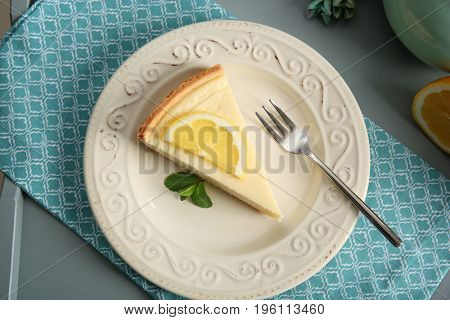 Ceramic plate with delicious cheesecake and fork on blue napkin