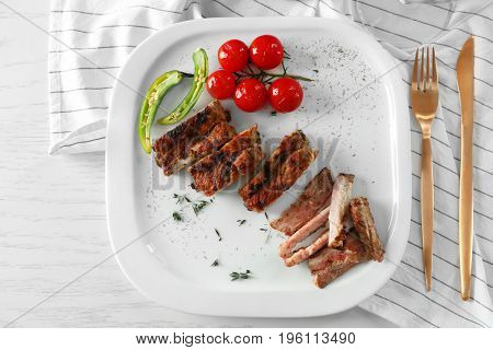 Yummy grilled sliced spare ribs with cherry tomatoes on square white plate, top view