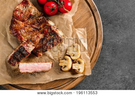 Yummy grilled spare ribs with mushrooms and cherry tomatoes on wooden board, top view