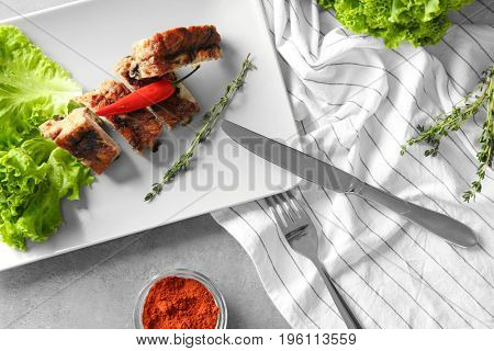 Delicious grilled sliced spare ribs with salad leaves and pepper on white plate