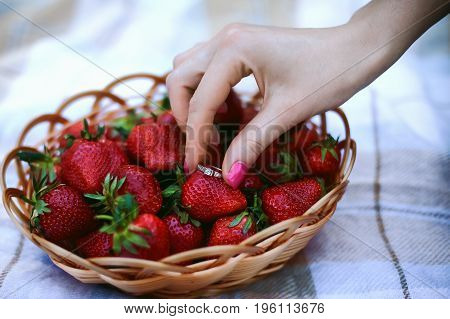 The girl's hand holds an engagement ring near a wicker basket with strawberries. Still life. concept of Betrothal, wedding, honeymoon