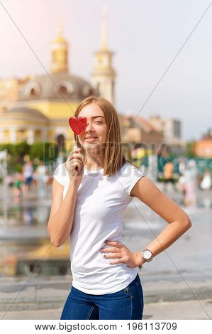 Smiling young woman with heart shaped lollipop outdoors