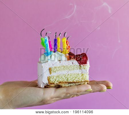 Girl holding beautiful appetizing birthday cake with many blown candles. Closeup.