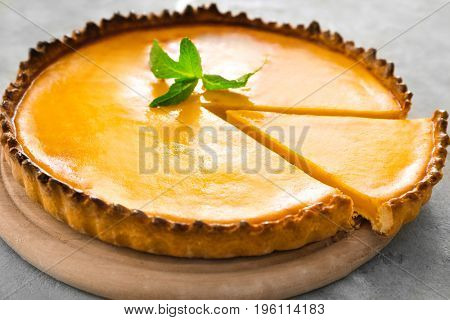 Wooden plate with delicious lemon cake on gray table, closeup