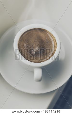 Tasty coffee espresso in small cup near window. Home concept. Top View. Toning.