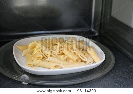 Plate of pasta with cheese in microwave