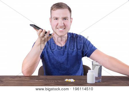 A disgusted boy with medicine isolated on a white background. A sick man in a dark blue shirt is angry and holding a phone. Painkillers, antibiotics in a bottle and a glass on a wooden table.