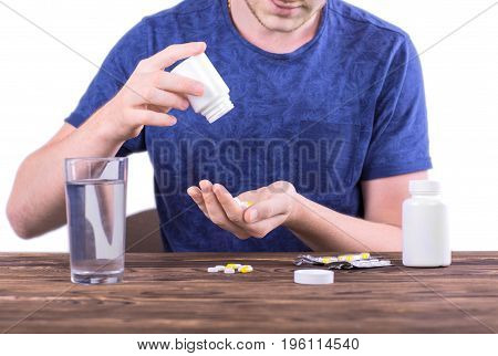 A man in a blue shirt taking medication isolated over the white background. A sick man sitting next to a brown table with medicaments on it. An ill guy pouring out drugs into his hands.