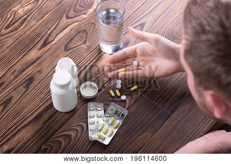 A top view of a young man looking at pills in his hand. Various drugs and painkillers in packs and a white bottle on a light brown table. A sick patient taking prescripted drugs.
