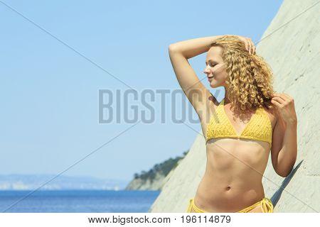 Beautiful blonde posing leaning against rock near ocean coast