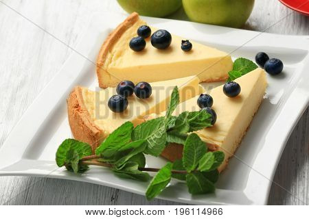 Plate with slices of delicious cheesecake and berries on wooden table