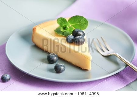 Plate with cheesecake, berries and fork on violet napkin