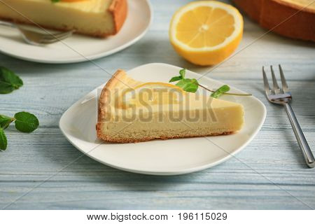 Plate with delicious cheesecake and slice of lemon on wooden table
