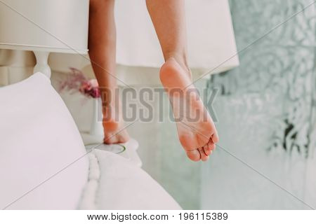 Beautiful bride in silk robe takes her dress from the cornice. Morning preparation before wedding. Slender legs of a charming girl. Bottom view