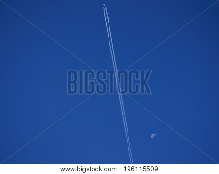 Modern airplane crossing the intense blue sky and the waning moon in the distance