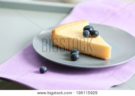 Plate with slice of delicious cheesecake and blueberry on violet napkin