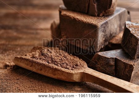 Wooden scoop with cocoa powder and chopped chocolate chunks, closeup