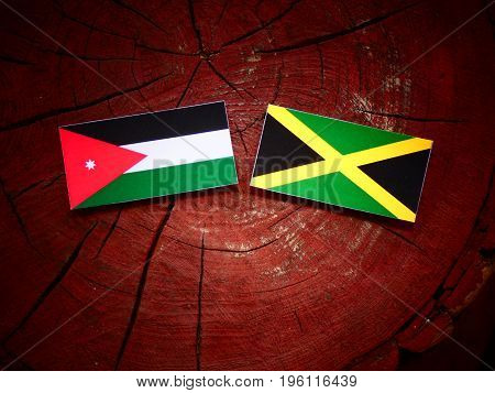 Jordanian Flag With Jamaican Flag On A Tree Stump Isolated