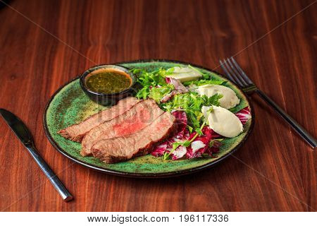 Sliced grilled beef steak with green leaves salad on rustic plate with cutlery. Medium rare barbecue steak and healthy salad