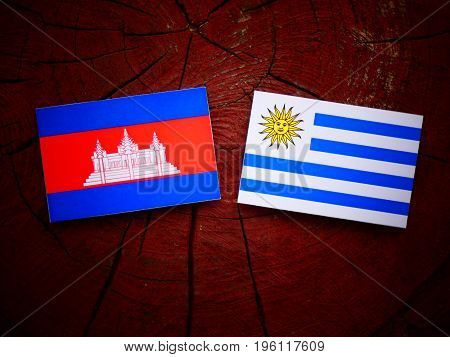 Cambodian Flag With Uruguaian Flag On A Tree Stump Isolated