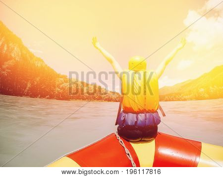 man sits on the edge of a rafting boat in rescued jelly and a protective helmet, rejoices, raises his hands up, rear view. Concept of active summer.