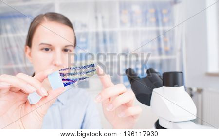 young woman scientific / female student researcher looking microscope slide  in a laboratory.