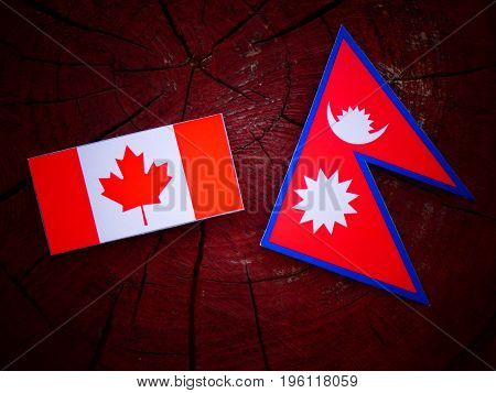 Canadian Flag With Nepali Flag On A Tree Stump Isolated