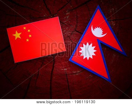 Chinese Flag With Nepali Flag On A Tree Stump Isolated