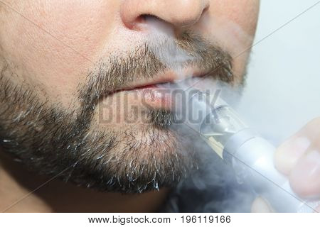 man smoking electronic sigarette close up with smoke