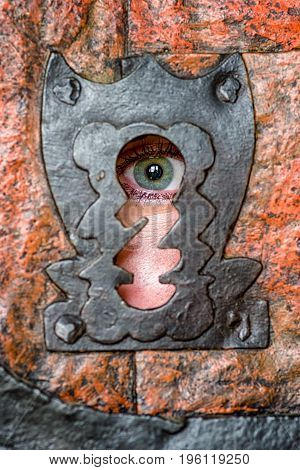 Human green eye spying through keyhole in doors