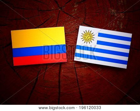 Colombian Flag With Uruguaian Flag On A Tree Stump Isolated