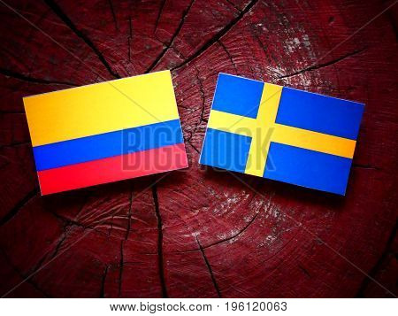 Colombian Flag With Swedish Flag On A Tree Stump Isolated