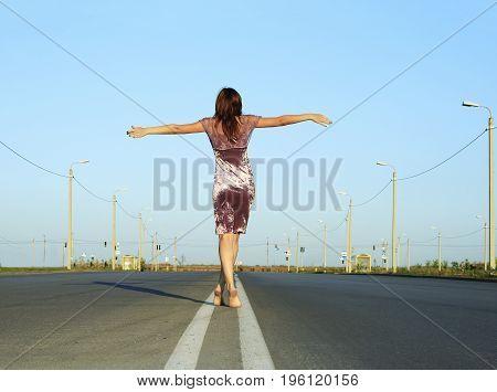 Beautiful female go away on empty road