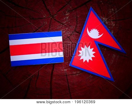 Costa Rican Flag With Nepali Flag On A Tree Stump Isolated